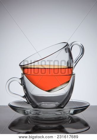 Glass Cups Of Tea On Saucer, Good Concept The Idea, On Grey Gradient Background.