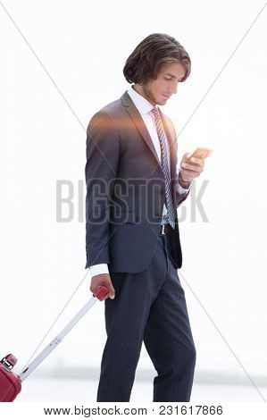 businessman with Luggage by reading SMS on smartphone