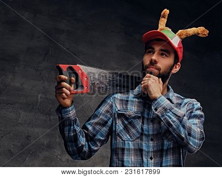 A Bearded Male In A Hat With Deer's Horns Holds Handsaw.