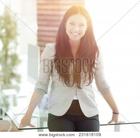 smiling modern business woman standing near a work table.