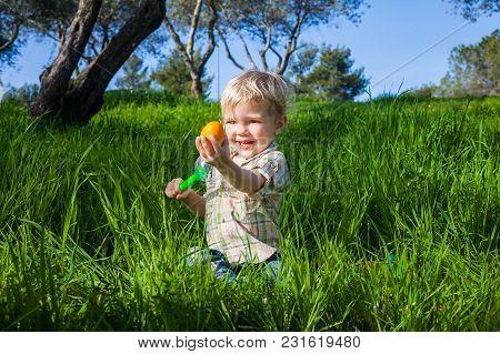 Toddler Boy Holds Up An Easter Egg