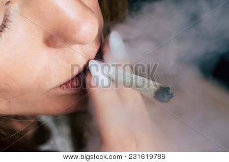 Smokes Weed Cannabis, A Woman Joint In His Hands. Smoke On A Black Background. Concepts Of Medical M