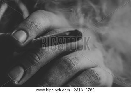 Joint In Man Hand. A Man Smokes Cannabis Weed, A . Smoke On A Black Background. Concepts Of Medical