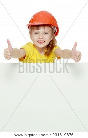A Nice Little Girl In A Construction Helmet And A Yellow T-shirt Peeped Out From Behind A White Adve