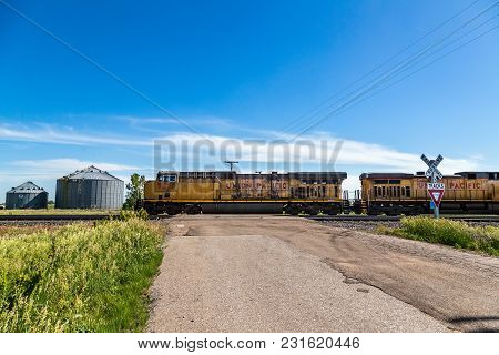 Lexington, Nebraska, June 12, 2013 Union Pacific Locomotives Lead A Train Across A Rural Grade Cross