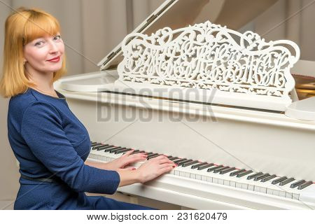 Beautiful Young Woman Near A White Grand Piano. The Concept Of Musical Education, Creative Developme
