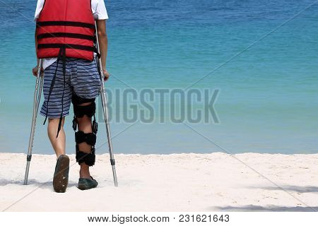 Disabled Man With Crutches While Travel On The Beach  Ocean Views Background.