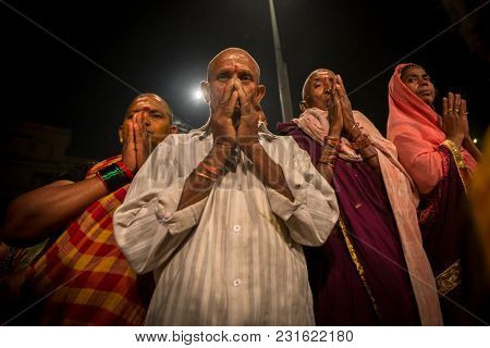 VARANASI, INDIA - MAR 15, 2018: Pilgrims during perform Agni Pooja (Sanskrit: Worship of Fire) on Dashashwamedh Ghat - main and oldest ghat of Varanasi located on the Ganges.
