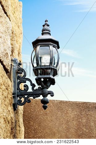 A Old Antique Lamp Made Of Brass On Castle Walls In Noon.