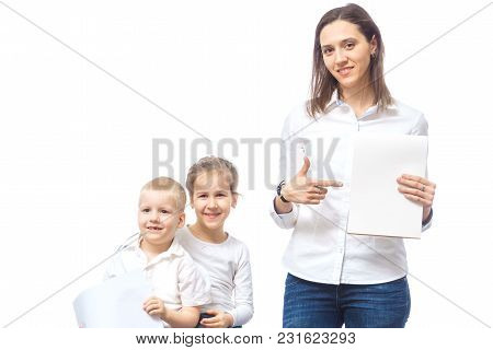 Young Family. Mother, Daughter And Son. The Mother Holds An Empty Sheet In Her Hands And Points At I