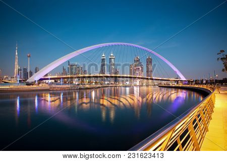 DUBAI, UAE - FEBRUARY 2018: Colorful sunset over Dubai Downtown skyscrapers and the newly built Tolerance bridge as viewed from the Dubai water canal.