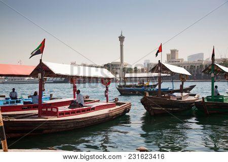 DUBAI, UAE- May 3, 2013: Traditional Abra ferries crossing Dubai Creek. The Creek divides the city into two main sections: Deira and Bur Dubai