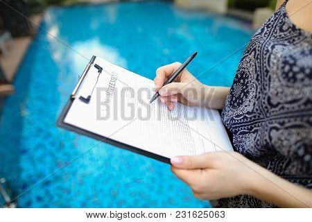 Photographed Close Hand Of Girl Signing Sunny Day Paper On Pool Background. Concept Of Signing Contr
