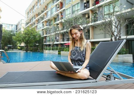 Young Female Woman Working With New Laptop Pc Computer Outdoors Remotely As Freelancer Close To Blue