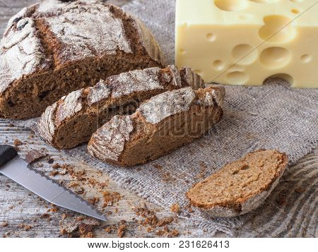 Homemade Bread From Rye And Wheat Flour With Cranberries And Cheese With Holes On An Old Wooden Tabl