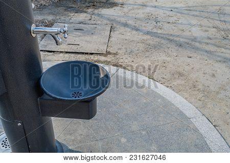 Black Metal Water Drinking Fountains Near Walkway In A Public Park
