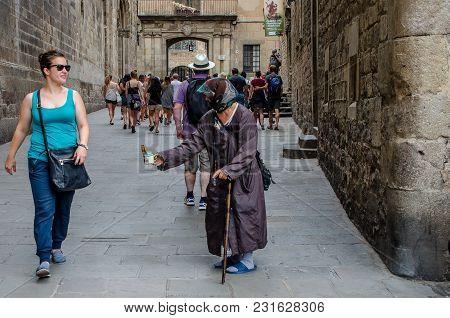 Elderly Beggar Girl In The Streets Of The City Of Barcelona In June 2016
