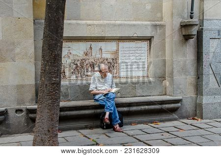 Elderly Man Reads The Newspaper Sitting On A Street In The City Of Barcelona In June 2016