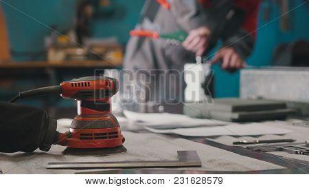 Manual Sander Sanding A Metal Detail At The Factory, De-focused, Industrial Concept
