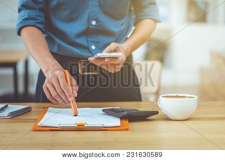 Business Man Working Document In Coffee Shop Morning Light.
