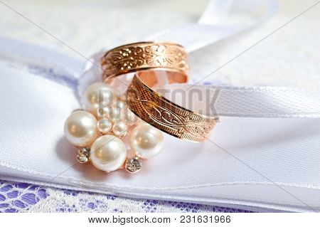 Two Gold Wedding Rings With Patterns On A Beautiful Cushion With Decorations