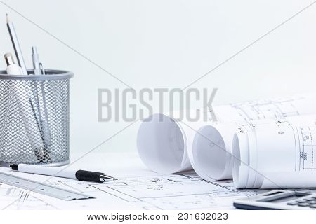 Blueprint Rolls With Construction Plans, Pencil, Ruler And Calculator, On Desk. Architect Workplace