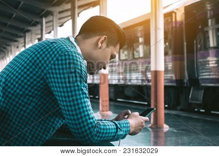 Rear View Of Young Asian Hipster Man Holding Mobile Phone Using App Song With Linten Music At Train
