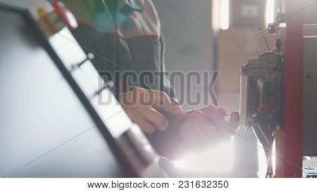Electrician Male In Overalls Is Working With Energy Panel And Machinery Equipment On Plant, Close Up