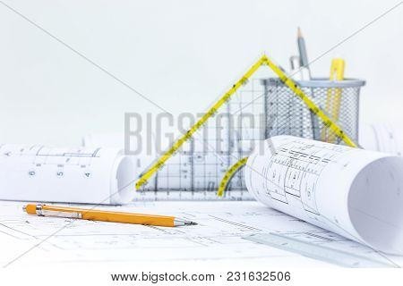 Architect Workplace With Rolls Of Blueprints And Technical Plans On Desk