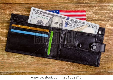 One Hundred Dollars Banknote Reach Out Out Of A Black Old Purse. And Also Part Of The American Flag.