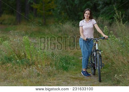 Young Woman Riding On Bicycle In The Forest. Leisure On Cycle, Active Lifestyle, Cycling In Park