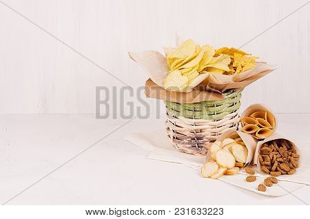 Different Crispy Golden Snacks In Wicker Basket And Paper Cones On Soft White Wood Background, With