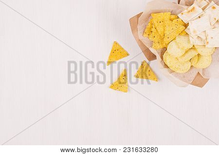 Heap Different Crispy Golden Snacks On Craft Paper, Triangles Nachos On Soft White Wood Background,