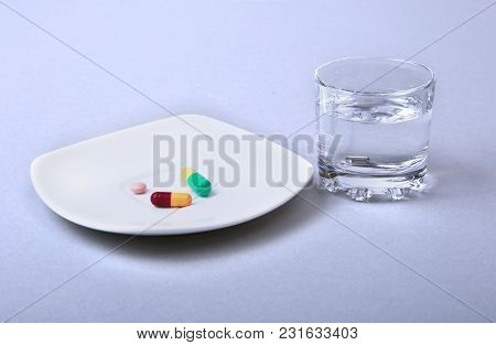 Glass Of Water And Pills On White Background.
