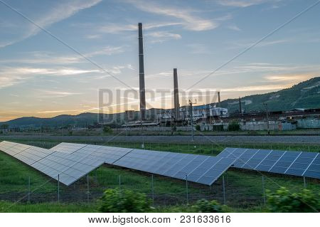 Solar Panels Near A Power Plant With Pipes.