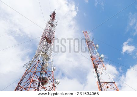 Two Telecommunication Tower On A Sunny Day Against A Blue Sky.
