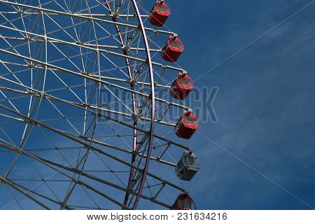 A Sight Of A Ferris Wheel With A Clear Blue Sky