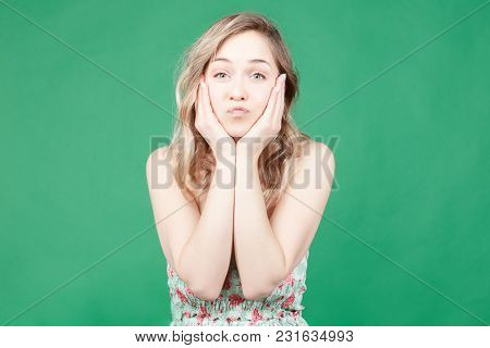 Young Adorable Blonde Female Expresses Her Love, Blows Kiss At Camera, Isolated Over Green Wall Back