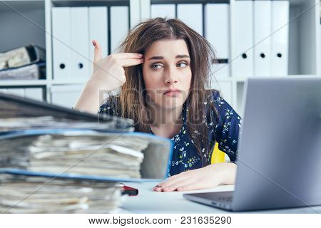 Business Woman Working With Her Laptop And Making Suicide Gesture In The Office