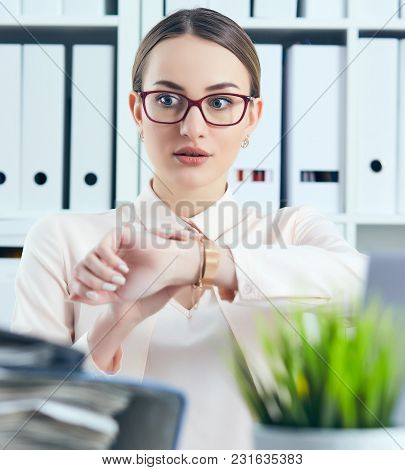Shocked Manager Looking At Her Watch Near A Pile Of Documents. Deadline Concept.