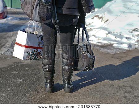A Woman Carrying Shopping Bag, Rucksack And Handbag, Filtered Horizontal Shot