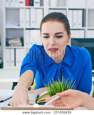 Two Woman Working At The Office While One Is Pointing At The Data At Clipboard. Startup Concept.