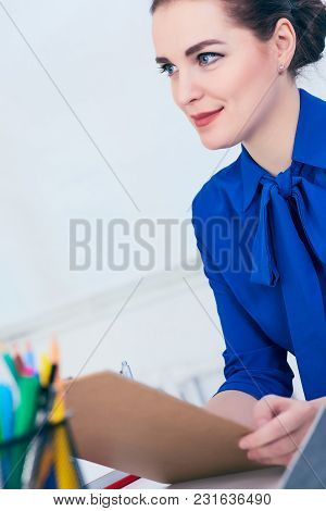 Young Caucasian Business Woman In Jacket Write On Clipboard At The Workplace In The Office.