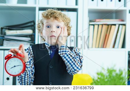 Disappointed Kid Boss Holding A Big Red Alarm Clock In His Hand Suggesting You Are Late For Work. Wo