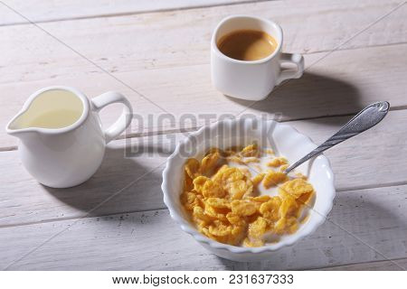 Corn Flakes Cereal In A Bowl, Glass With Milk And Cap With Espresso Coffee. Morning Breakfast