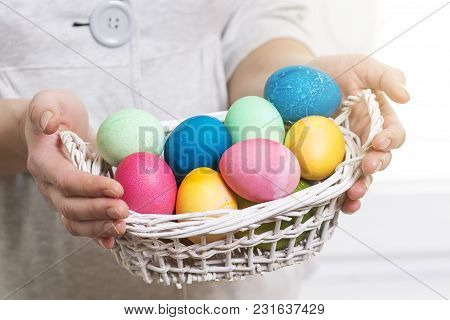 Easter Concept. A Woman Holds Basket With Colorful Colored Eggs For Religious Easter Holiday. Easter
