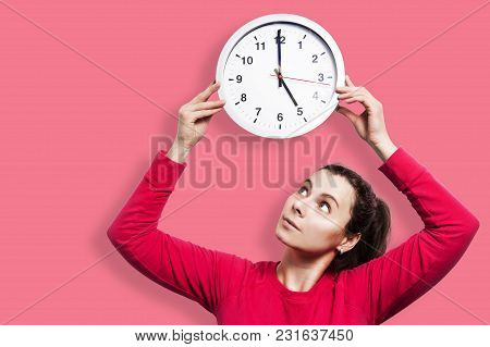 Beautiful Brunette Girl Holding Round Watch Clock. Time Concept. Young Attractive Girl Is Looking At