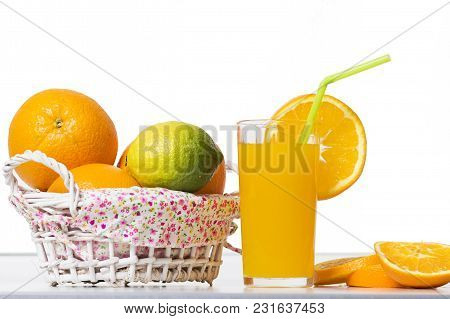 Fresh Orange Juice In A Glass Beaker, Slices Of Sliced Oranges And Basket On Table Isolated On White