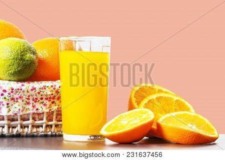 Fresh Orange Juice In A Glass Beaker, Slices Of Sliced Oranges And Basket With Oranges Isolated On A