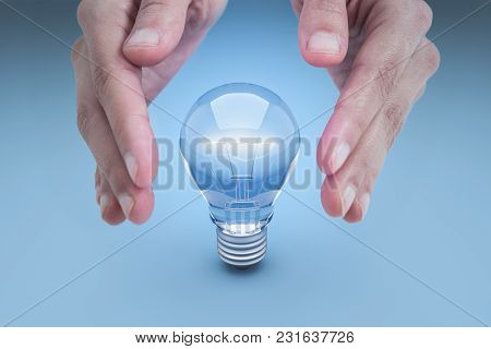 Hand And Energy Saving Lamp On A Blue Background.